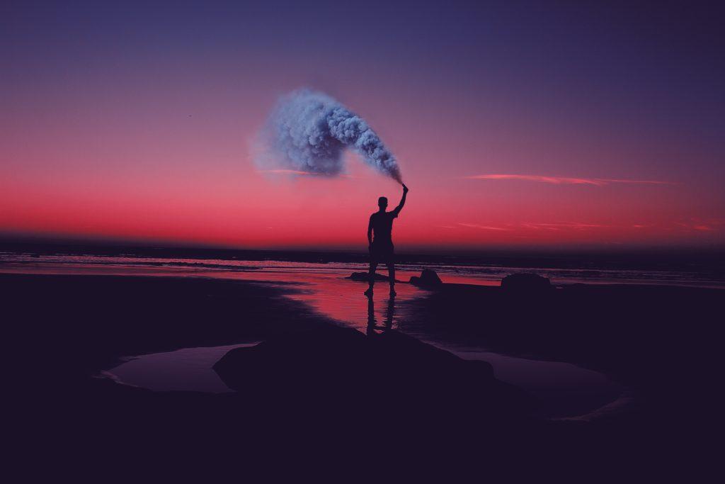 どこかで発煙筒で合図してる男性