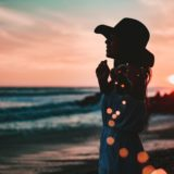海辺で夕日を眺めてる女性