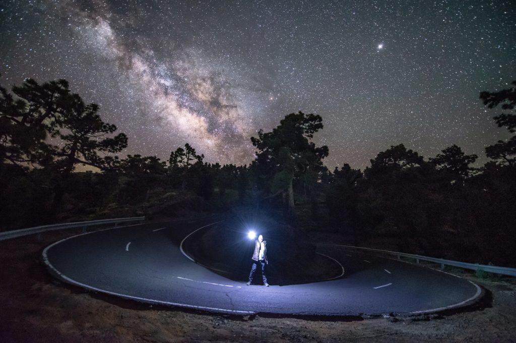 夜空の下で懐中電灯照らしてる男性