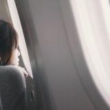 飛行機の窓からのぞいてる女性