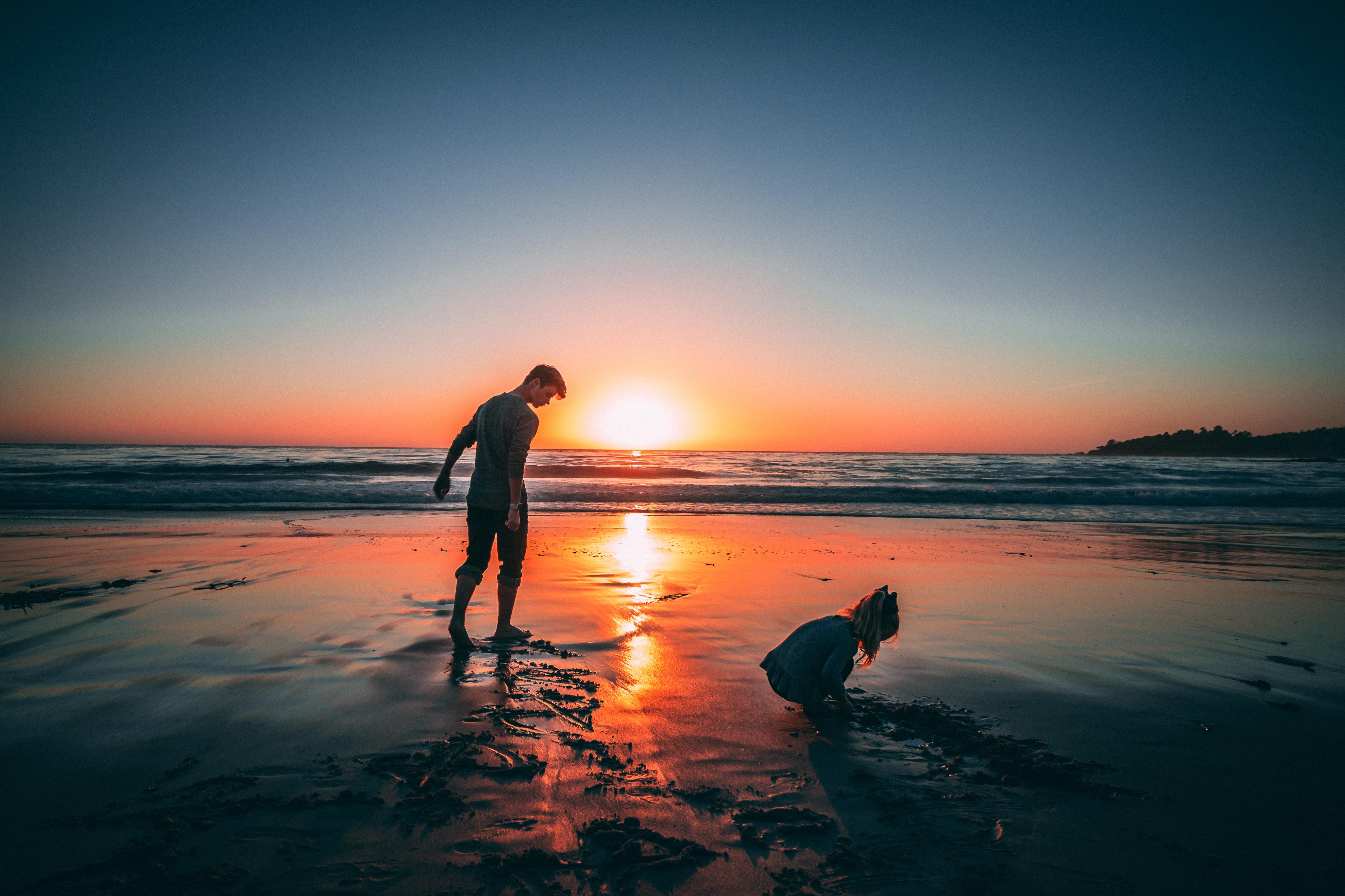 夕焼けのもとで遊ぶ親子