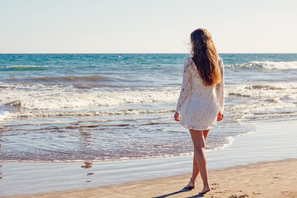海が背景の後ろ姿の白い服の女性