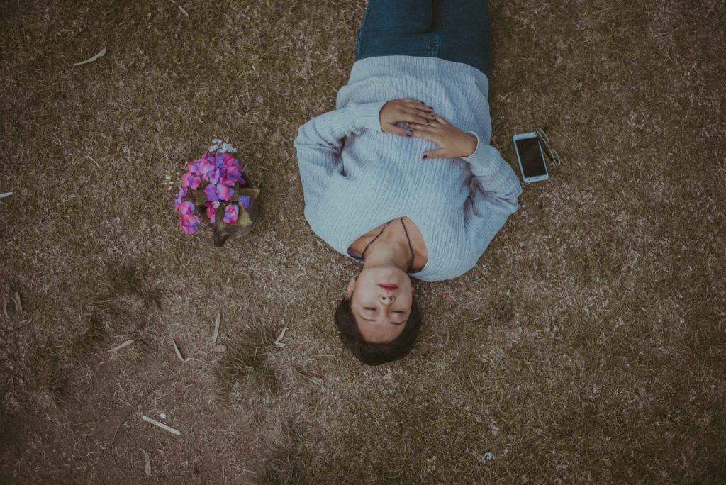 墓のとなりで寝てる女性